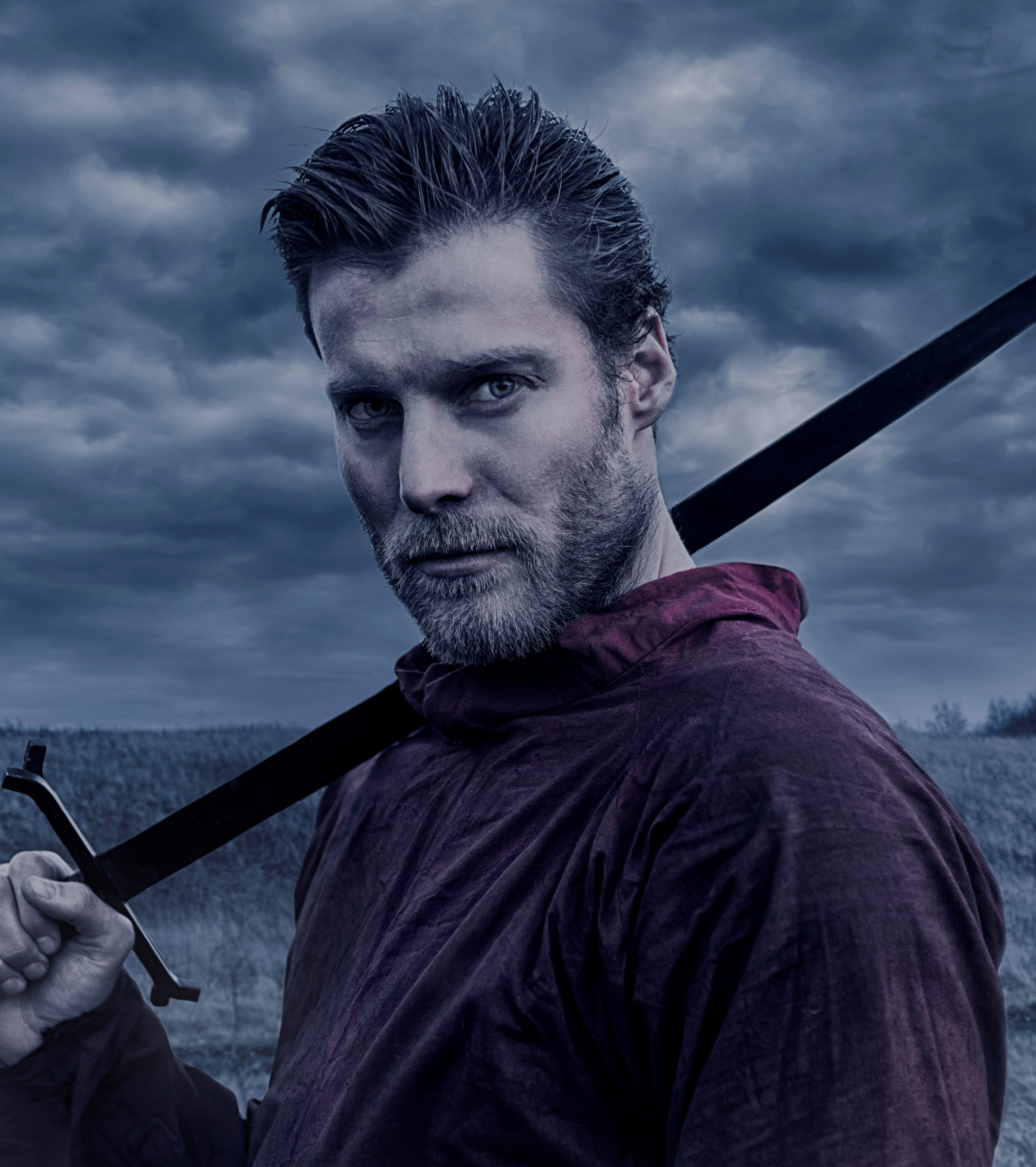 Man with beard and historic clothes holds a sword. He is in his 30s and resembles a viking warrior or a knight. He is holding a long sword, which is resting on his shoulder. Dark landscape in the background with a lonely tree.